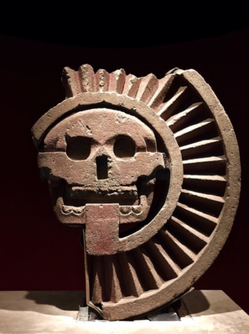 Stone figure of a skull surrounded by rays from Teotihuacan, Mexico