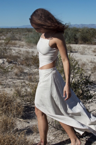 Sophie walking through the dry desert in a long, white linen dress