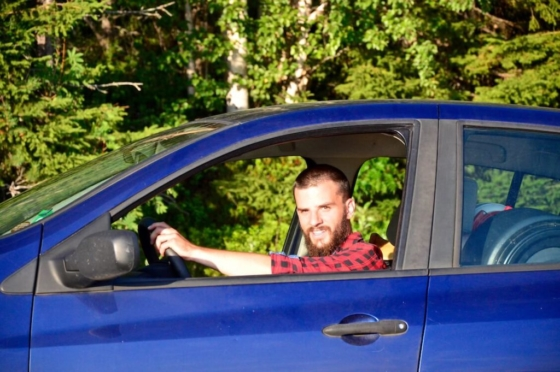Peter sitting at the steering wheel of our tiny blue car and smiling out of the window