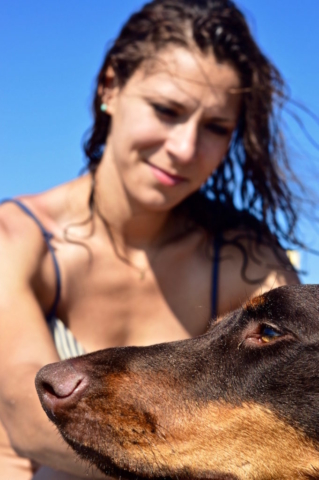 Sophie and Merida her doberman enjoying the warm sun at the beach