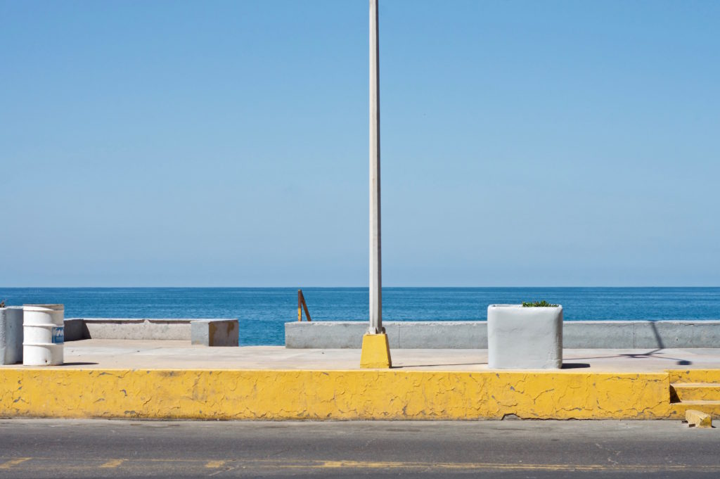 The horizon, the pacific ocean and the yellow sidewalk lining up