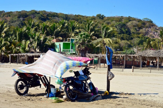 An awning at the beach made with two motorbikes and an old blanket