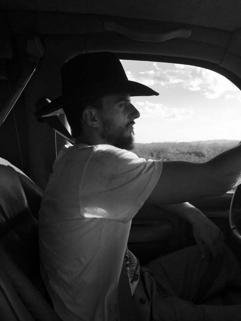 Peter with a cowboy hat driving the big van