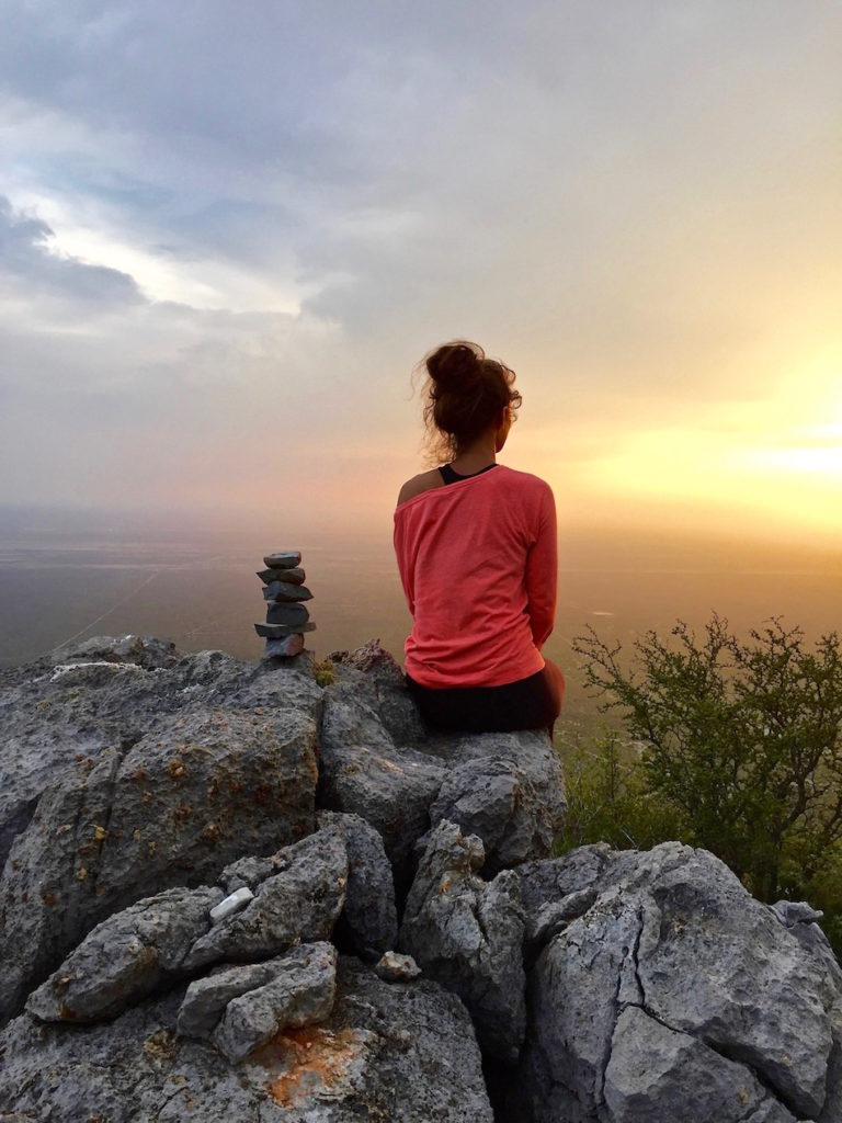 Sophie sitting next to a stone cairn on top of a mountain watching the sun set