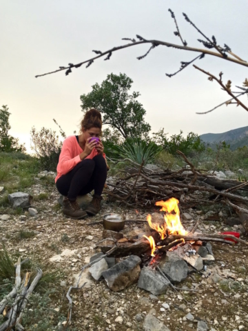 Sophie drinking tea in front of our campfire