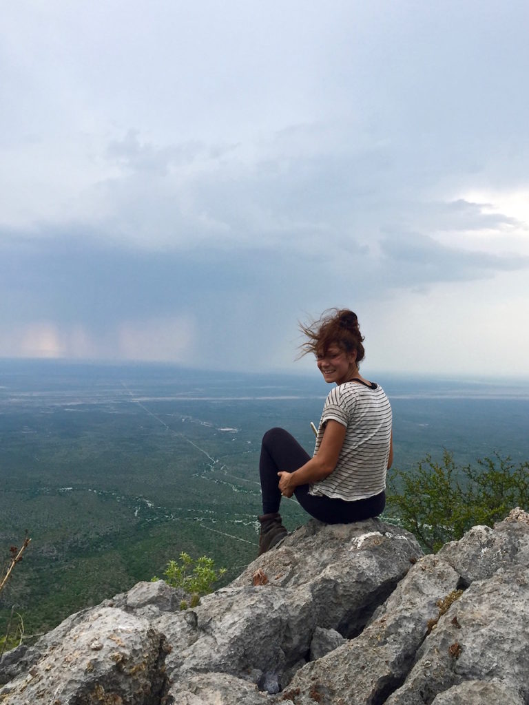 Sophie on a mountaintop overlooking the plains and rain in the distance