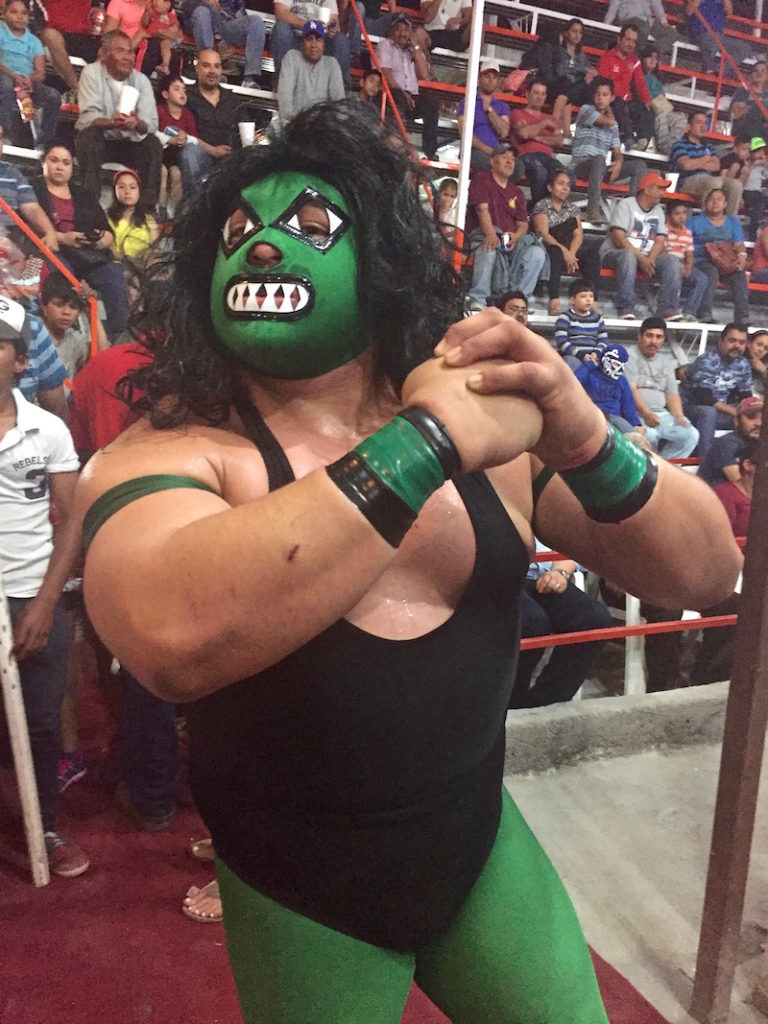 Mexican lucha libra wrestler with his mask posing for the crowd