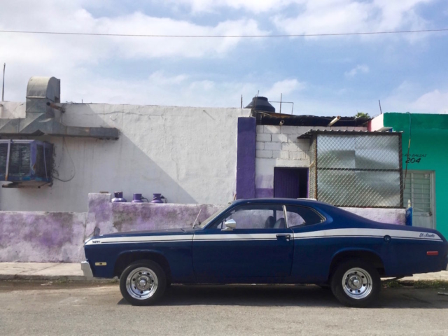 An old, blue muscle car in front of a purple, green and white house in Mexico