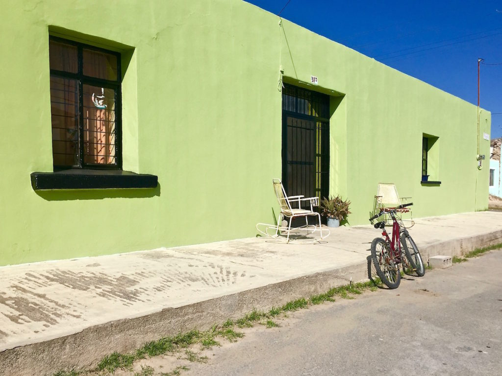 a bike leaning against a green house in a lonely Mexican street