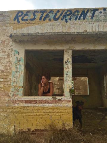 Sophie and her doberman Merida standing inside an abandoned restaurant