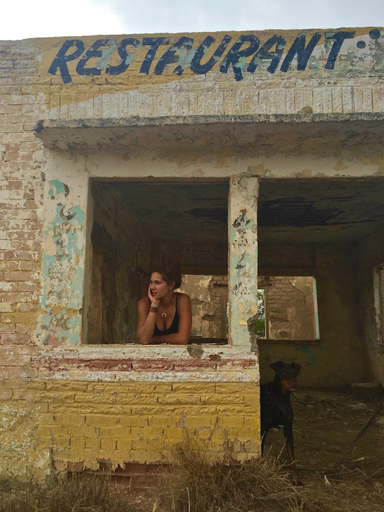 Sophie and her doberman Merida standing inside an abandoned restaurant