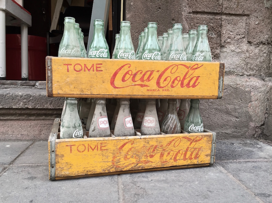 Empty Coca-Cola bottles in a wooden tray