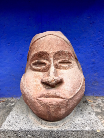 Big stone head in front of a blue wall inside Frida Kahlo's house