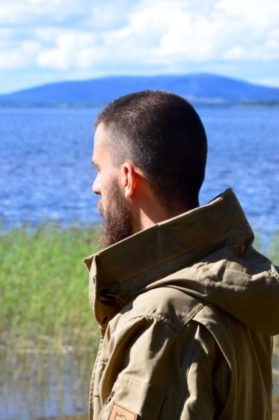 Peter in his Fjällräven jacket overlooking the lake with seaweed in the front and the blue mountains in the back