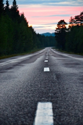 The wet road through the deep forests in Lapland, Sweden while the sun sets and lights the sky red