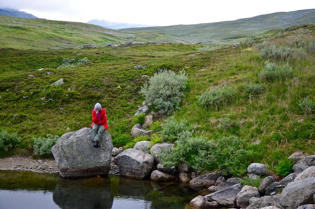 Sophie in her red Fjällräven jacket sitting on a big rock at a small pond in the mountains of Lapland, Sweden