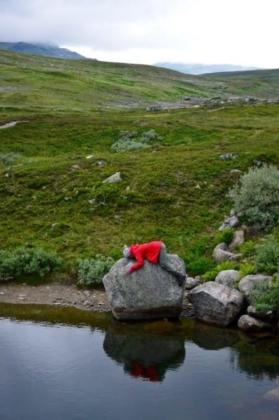 Sophie sleeping in her red Fjällräven jacket on a big rock at a small pond in the mountains of Swedish Lapland