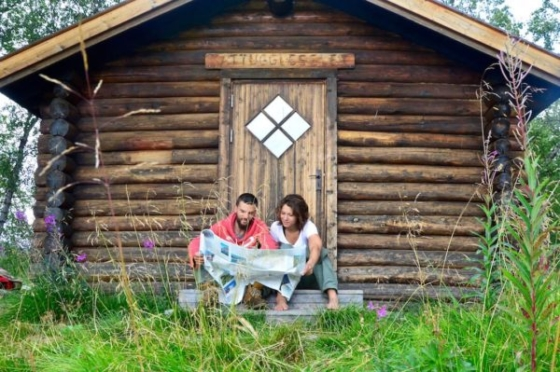 Sophie and Peter sitting in front of a wooden cabin and studying the map