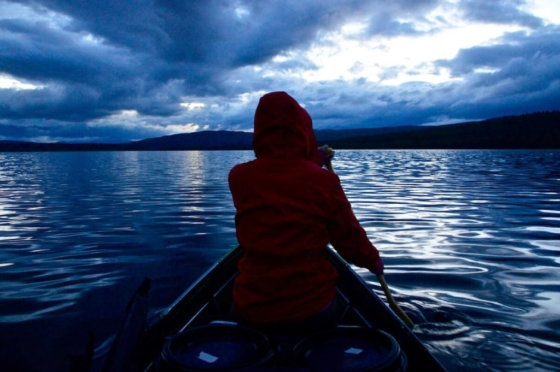 Sophie in her red Fjällräven jacket paddling out into the deep blue lake in front of the canoe at midnight in the Swedish summer