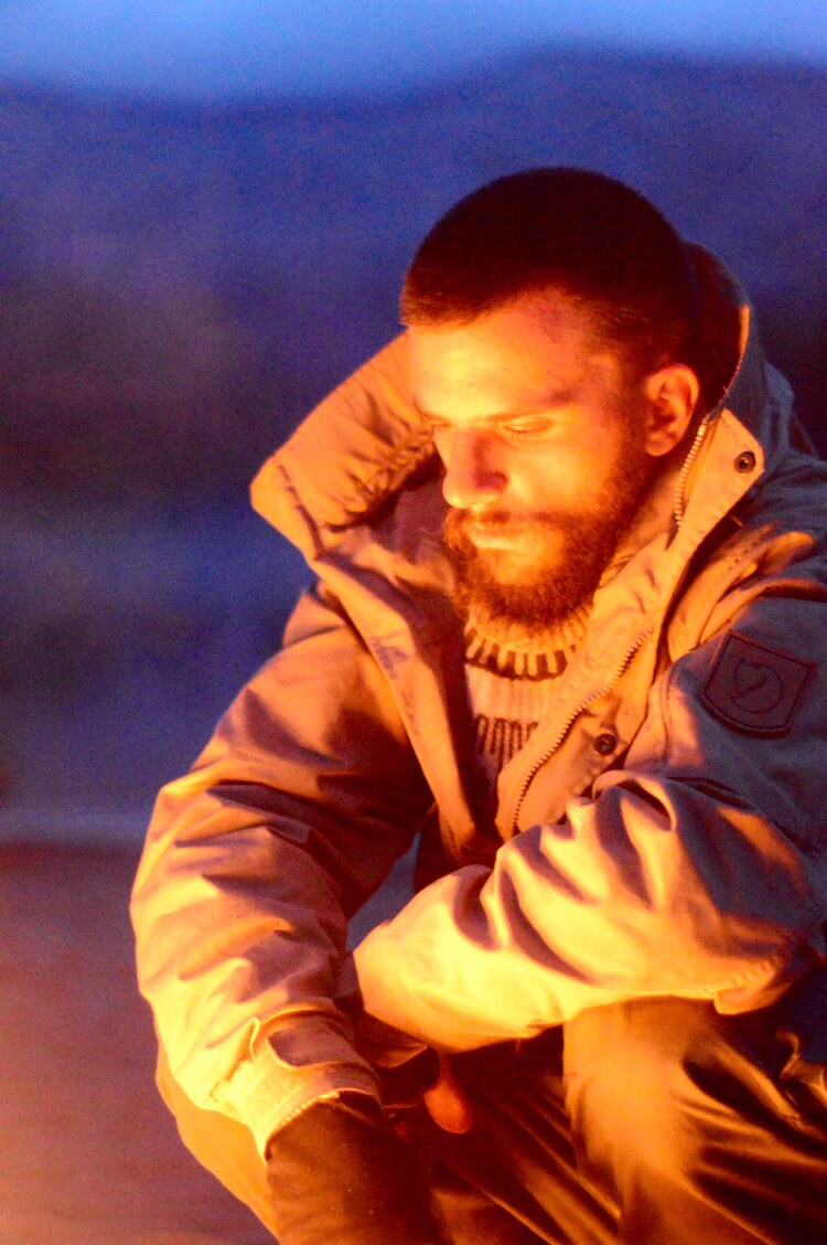 Peter starring in the fire at night with his Fjällräven jacket