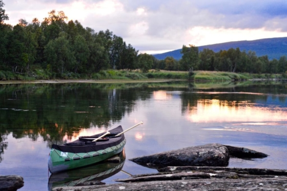 Our green Ally canoe at the river shore at sunset with the forest and the mountains in the back