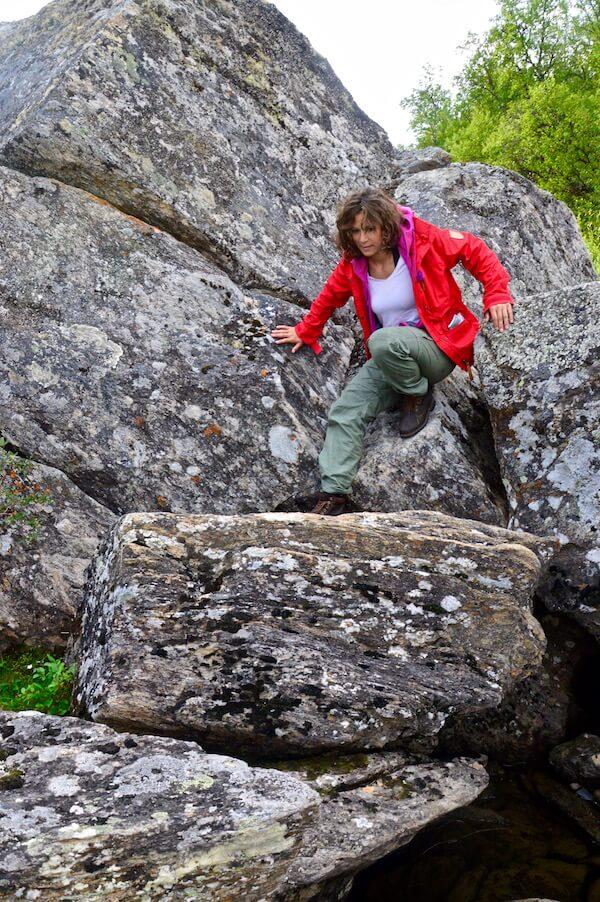 Sophie in her red Fjällräven jacket climbing over the rocks
