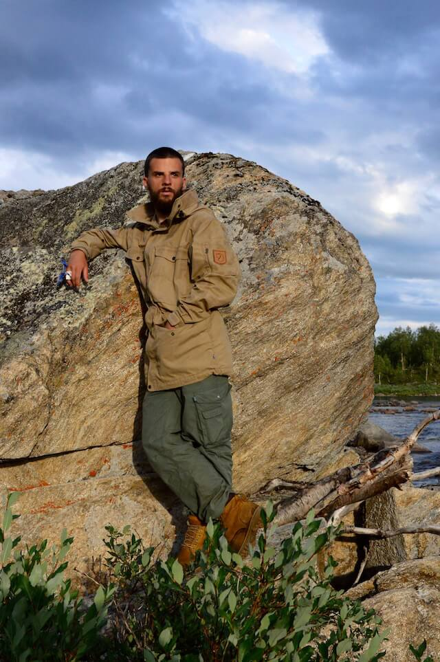 Peter in his Fjällräven jacket leaning against a rock in the golden hour in front of a cloudy sky