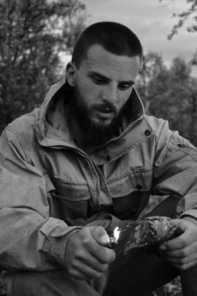 Peter in his Fjällräven jacket captured in black and white while lighting a birch bark