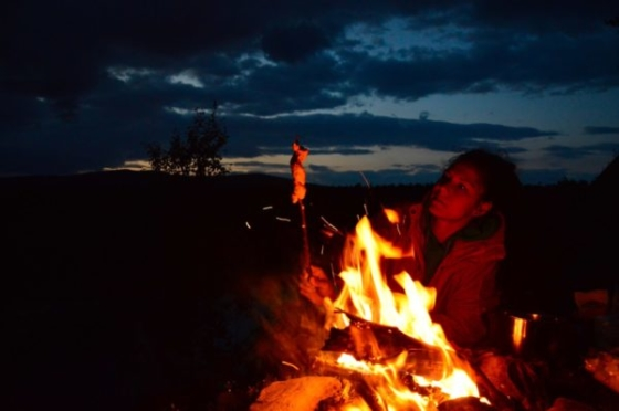 Sophie roasting her bread on a stick over the fire at night in Lapland, Sweden