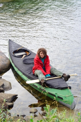 Sophie sitting on top of our spray cover in the canoe and smiling happily Lapland, Sweden