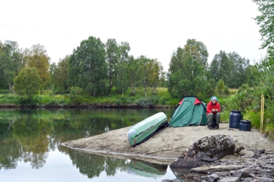 Sophie sitting on a small sandy island right next to our Ally canoe and our tiny tent in Lapland, Sweden