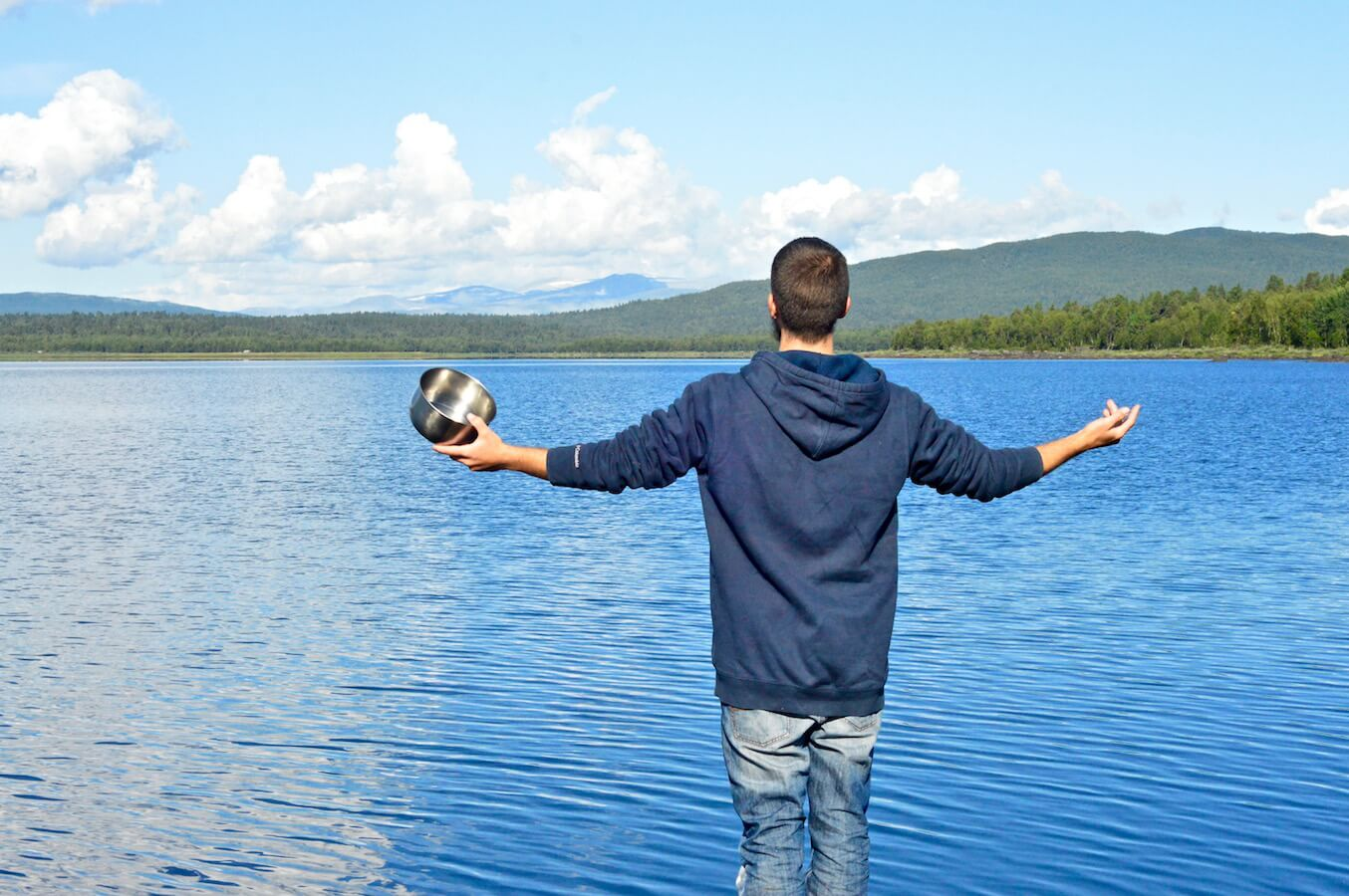 Peter spreading his arms in front of the blue lake in the morning in Lapland, Sweden