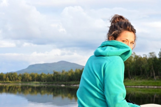 Sophie in her green Bergans of Norway fleece looking back into the camera while the light is golden and the river quiet in Lapland, Sweden