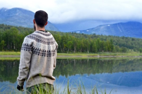 Peter in a Norway pullover watching the blue reflections of the birches and the mountains in the river after sunset in Lapland, Sweden