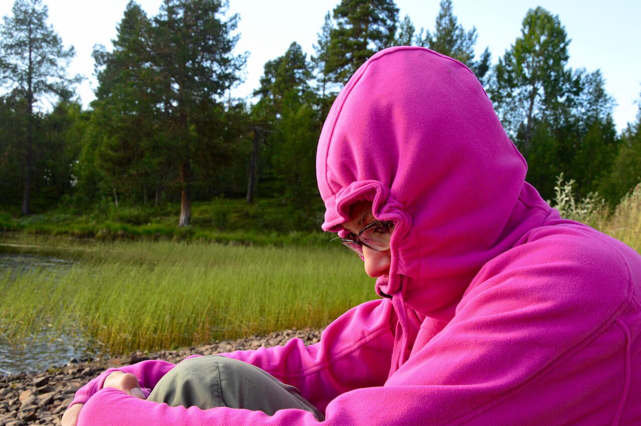 Sophie seeking shelter in her pink fleece hoody to avoid mosquito bites in Lapland, Sweden