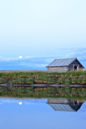 A simple wooden cabin and the full moon reflecting in the quiet water of the river in Lapland, Sweden