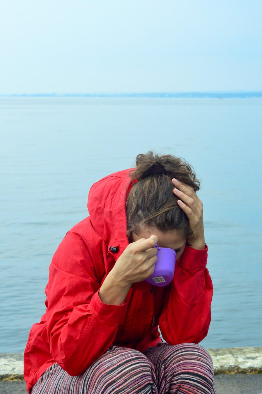 Sophie in her red Fjällräven jacket in front of a light grey lake and a light grey sky drinking out of a purple cup in Sweden