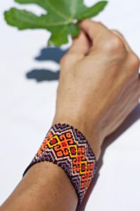 Mexican patterned bracelet on a woman's wrist holding a fig tree leave
