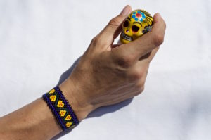 Woman's hand with a Mexican bracelet holding a painted ceramic skull