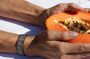 Papaya held by two hands with a Mexican bracelet