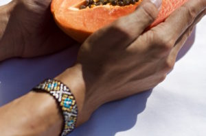 Papaya on a white sheet held by a hand with a Mexican bracelet