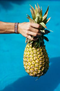 Holding a pineapple over the water with a Mexican bracelet on the wrist