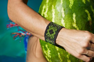 Holding a huge watermelon with a Mexican bracelet on the wrist