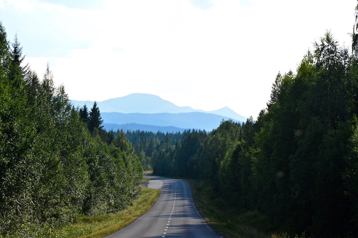 The road with deep forest on both sides and the blue mountains in the far distance in Lapland, Sweden