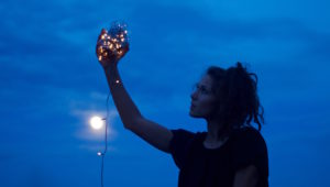 Girl holding fairy lights in the dark sky with full moon