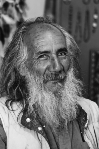 Old Mexican craftsman with his weathered face and wild beard smiling for the camera