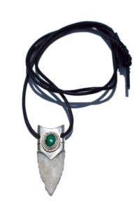 A granite arrowhead lined in silver and a malachite jewel on a leather cord