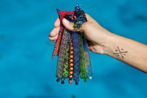 Handmade Mexican bracelets held in a bundle over a blue swimming pool