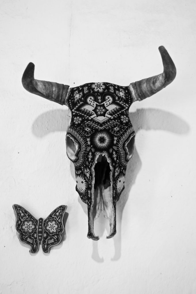 Skillfully decorated skull of a bull next to a carved butterfly
