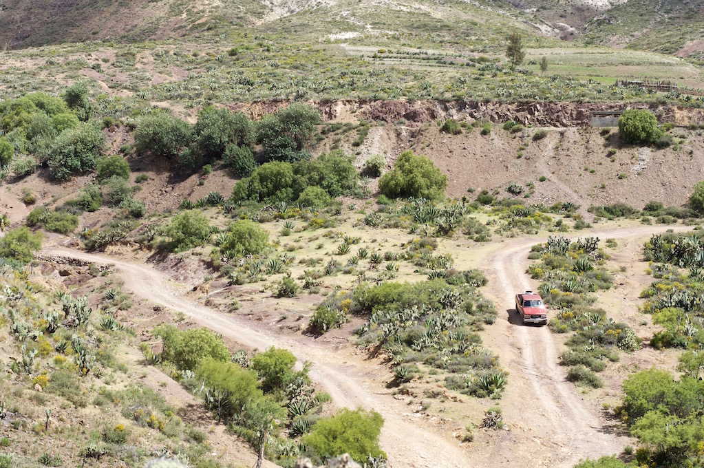 Old, red Pick up crossing the sparse landscape around Real de Catorce, Mexico